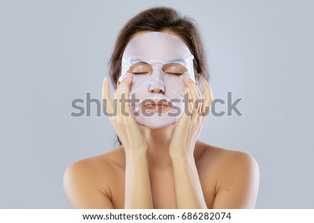 Face care and beauty treatments. Woman with a cloth moisturizing mask on her face isolated on gray background #686282074