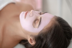 Face care. Young woman lying down with a mask on her face