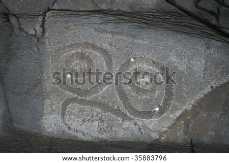 Face carved into a rock at Petroglyph Beach State Park at Wrangell, Alaska