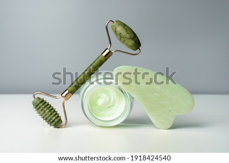 Face cream and jade massage roller. Lifting for healthy and youthful skin. Organic cosmetics on a black background.  Trending skin care. Gouache scraper for face and neck massage