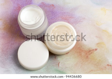 Face cream jars in coloured background