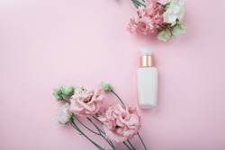 Face cream with fresh pink and white flowers, flatlay on pink background with plenty of copy space. Skin care and ati-ageing cosmetic concept