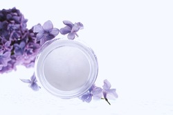 Face cream with lilac flowers on white background