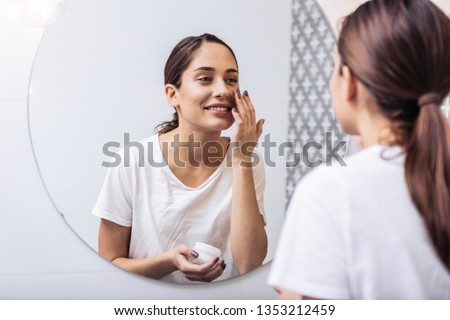 Face cream. Young beautiful woman wearing white shirt putting face cream on her nice healthy skin