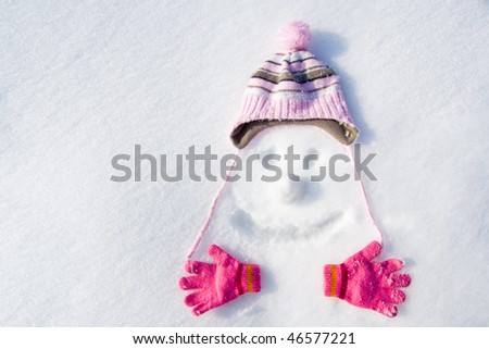 Face drawn in snow with cap, gloves and snowball.