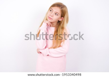Face expressions and emotions. Thoughtful beautiful caucasian little girl wearing pink sweater over white background holding hand under his head, having doubtful look.
