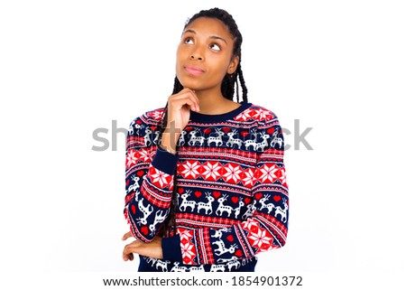 Face expressions and emotions. Thoughtful Young beautiful African American woman wearing Christmas sweater against white wall,  holding hand under his head, having doubtful look.