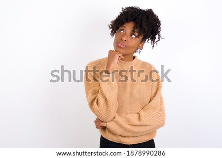 Face expressions and emotions. Thoughtful Young beautiful African American woman wearing knitted sweater against white wall holding hand under his head, having doubtful look.