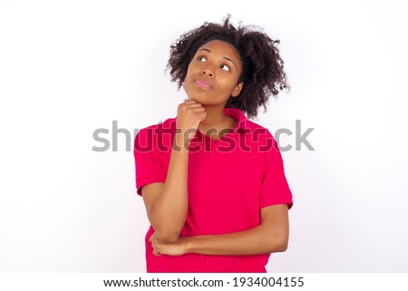 Face expressions and emotions. Thoughtful young beautiful African American woman wearing pink t-shirt against white wall holding hand under his head, having doubtful look.