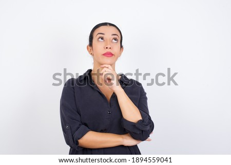Face expressions and emotions. Thoughtful young beautiful Arab woman wearing gray dress against white studio background holding hand under his head, having doubtful look.