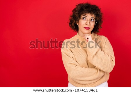 Face expressions and emotions. Thoughtful Young beautiful Arab woman wearing knitted sweater standing against red background holding hand under his head, having doubtful look.