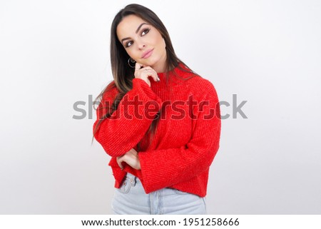 Face expressions and emotions. Thoughtful young beautiful brunette woman wearing red knitted sweater over white wal holding hand under his head, having doubtful look.