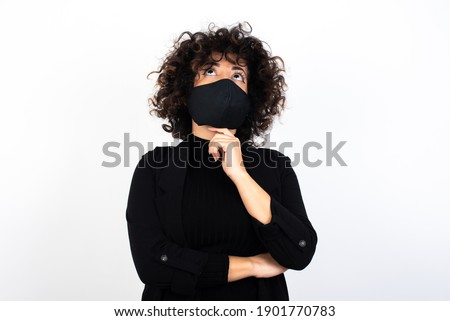 Face expressions and emotions. Thoughtful young beautiful caucasian woman wearing medical mask standing against white wall holding hand under his head, having doubtful look.
