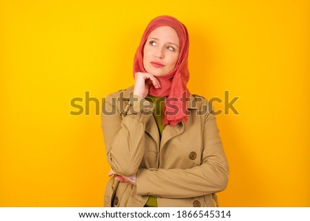 Face expressions and emotions. Thoughtful Young beautiful muslim woman wearing hijab against yellow background holding hand under his head, having doubtful look.