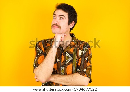 Face expressions and emotions. Thoughtful Young caucasian man wearing generic pattern printed shirt against yellow wall holding hand under his head, having doubtful look.