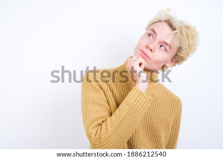 Face expressions and emotions. Thoughtful Young handsome Caucasian blond man standing against white background holding hand under his head, having doubtful look.