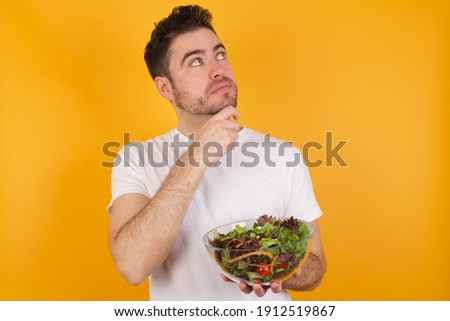 Face expressions and emotions. Thoughtful Young handsome Caucasian man holding a salad bowl against yellow background holding hand under his head, having doubtful look.