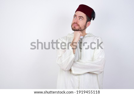 Face expressions and emotions. Thoughtful young handsome Caucasian man wearing Arab djellaba and Fez hat over white wall holding hand under his head, having doubtful look.