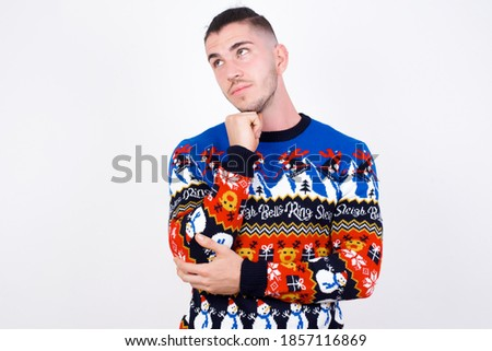 Face expressions and emotions. Thoughtful Young handsome Caucasian man wearing Christmas sweater against white wall, holding hand under his head, having doubtful look.