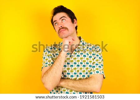 Face expressions and emotions. Thoughtful young handsome Caucasian man wearing Hawaiian shirt against yellow background holding hand under his head, having doubtful look.