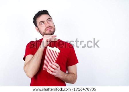 Face expressions and emotions. Thoughtful Young handsome man in red T-shirt against white background eating popcorn holding hand under his head, having doubtful look.