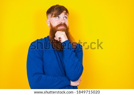 Face expressions and emotions. Thoughtful Young handsome red haired bearded Caucasian man standing against yellow wall holding hand under his head, having doubtful look.