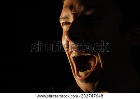 Face furiously screaming man on a black background