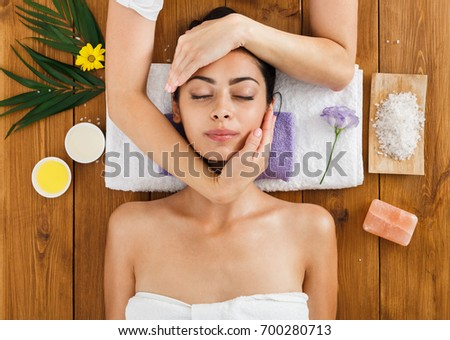 Face lifting massage in indian aroma spa wellness center to beautiful girl in cosmetology cabinet or beauty parlor. #700280713