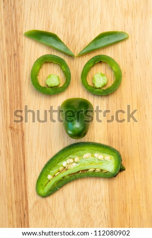 Face made of jalapeno pepper pieces showing the emotion of anger