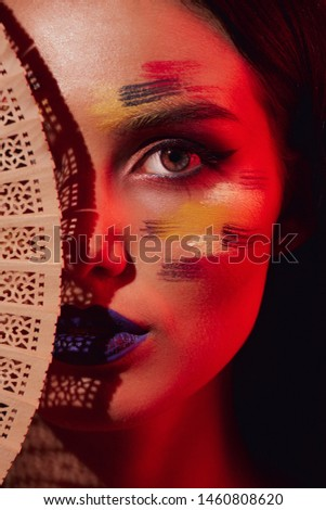 Face makeup and light art. Color painted beauty mysterious portrait lit with red light with shadow from hand fan. Danger concept. Mystery concept. Dangerous stranger.