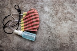 Face mask and Spray bottle of hand sanitizer on texture background , Everyday carry essentials of Covid-19 pandemic