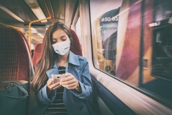Face mask concept. Woman wearing mandatory mask inside public spaces for transport such as train station and bus. Asian woman passenger using mobile phone with face covering on commute.