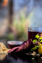Face mask for a natural glow for all skin types on the black wooden surface consisting of some beetroot juice, yogurt, lime juice, and gram flour. Shot of face mask with entire ingredients.