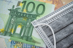 Face mask on Euro banknotes bill background. Global novel coronavirus (Covid-19) outbreak effect to EU, world economy, financial crisis, investment, stock market. Coronavirus pandemic in Europe, Euro.