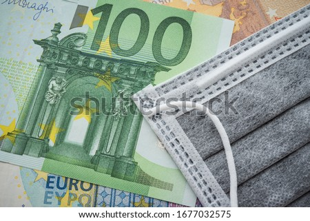 Face mask on Euro banknotes bill background. Global novel coronavirus (Covid-19) outbreak effect to EU, world economy, financial crisis, investment, stock market. Coronavirus pandemic in Europe, Euro.