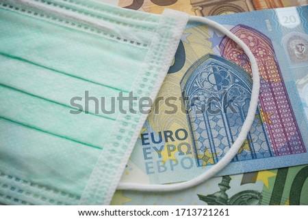 Face mask on Euro banknotes bill background. Global novel coronavirus (Covid-19) outbreak effect to EU, world economy, financial crisis, investment, stock market. Coronavirus pandemic in Europe.