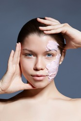 Face masks are the perfect treatment to hydrate skin, remove excess oils and improve the appearance of pores. A young lady with slicked brown hair is exhibiting her face with applied pink creamy mask.