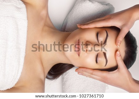Photo of Face massage.  Close-up of young woman getting spa massage treatment at beauty spa salon.Spa skin and body care. Facial beauty treatment.Cosmetology.