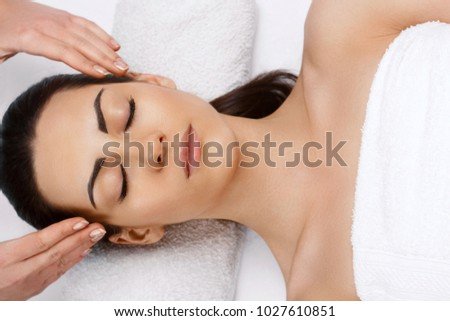 Face massage.  Close-up of young woman getting spa massage treatment at beauty spa salon.Spa skin and body care. Facial beauty treatment.Cosmetology. #1027610851