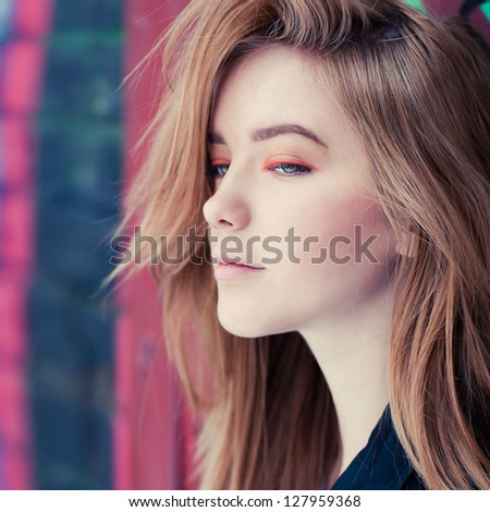 face of a beautiful young girl on the background of graffiti