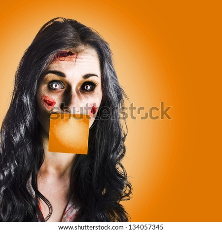 Face of a female office assistant overworked to death with a orange sticky notepad over mouth in a hard work conceptual - stock photo