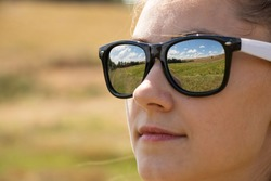 face of a girl in sunglasses closeup, reflections in glasses of the field and sky in summer
