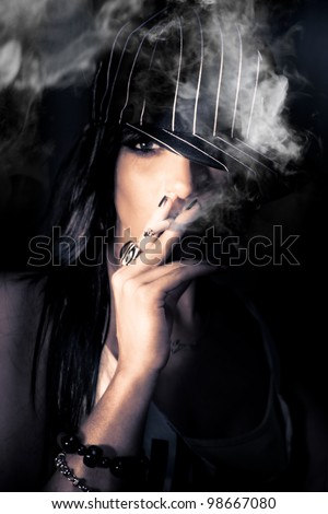 Face Of A Mysterious Urban Woman In Striped Cap Standing In The Shadows Of Darkness Smoking A Cigarette In A Sneak Smoke Conceptual, Focus On Cigarette Ash - stock photo