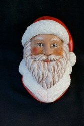 Face of a Santa Claus with beard and red cap. Close up, isolated on black background.
