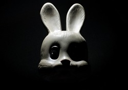 Face of a scary rabbit toy in the dark
