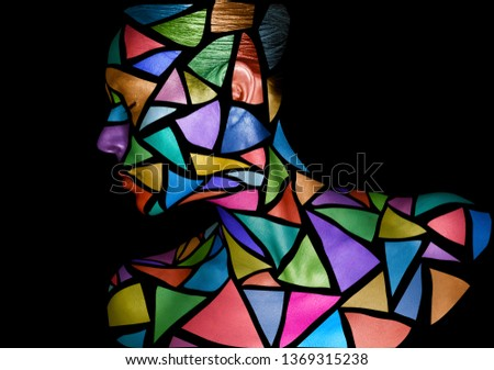 Face of a young female with creative body art. Colorful mosaic of triangles on the face of a woman, on black background.