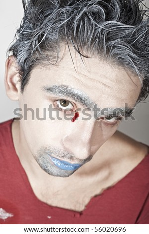 Face of a young guy with blue lips and bloody tears