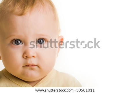 Face of adorable baby looking at camera seriously over white background