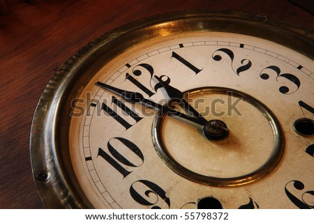 Face of an antique clock; indicating nearly midnight