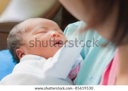 Face of Asian female newborn fall asleep in mother's arms